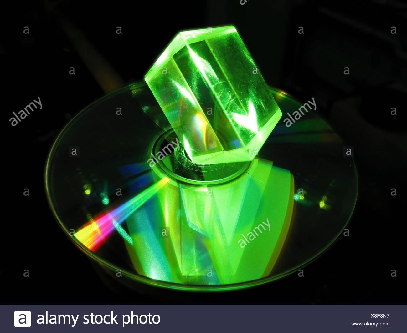Prisma de vidrio y láser. Prisma de vidrio iluminado con luz láser verde, con un reflejo visto en un disco óptico. Discos compactos (CD) y los discos versátiles digitales (DVD) son ejemplos de discos ópticos. Prismas de vidrio óptico son dispositivos utilizados para refractar y di Foto de stock