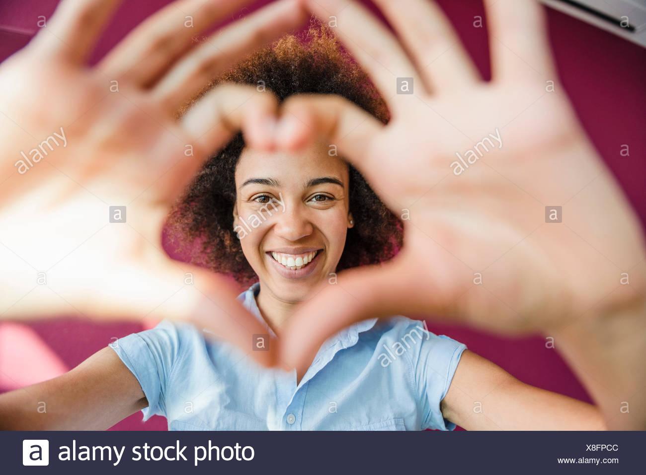 Retrato de mujer joven haciendo forma de corazón con las manos y los dedos Imagen De Stock