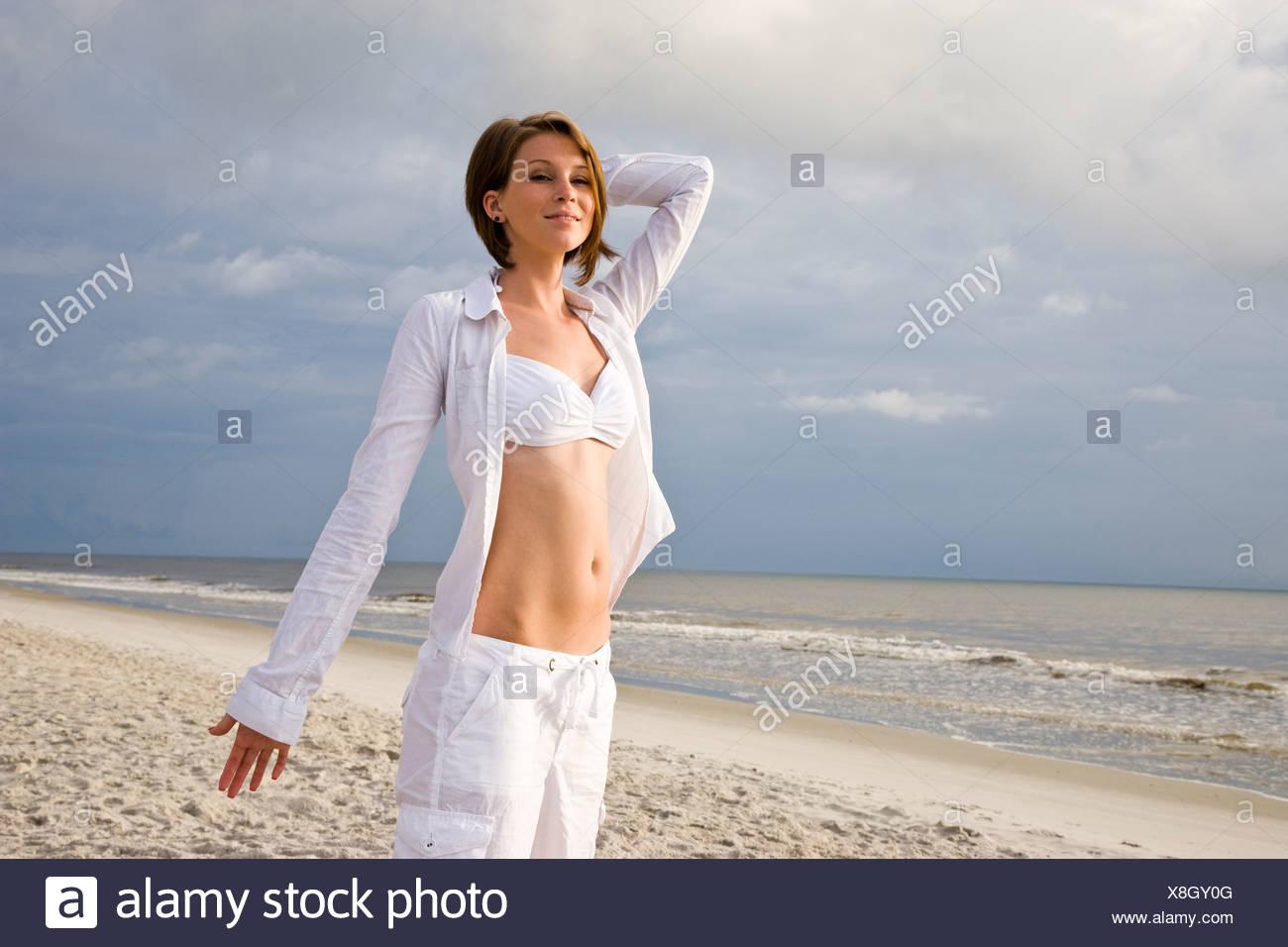 Retrato De Joven Mujer Feliz En Bikini Blanco Y Pantalones De Pie En La Playa Fotografia De Stock Alamy