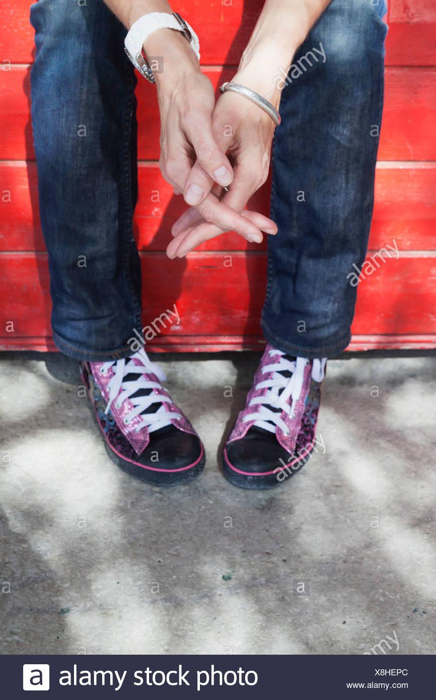 Mujer sentada con las manos entrelazadas y los dedos de los pies orientadas hacia el interior sugiriendo el desánimo con su lenguaje corporal; España Imagen De Stock
