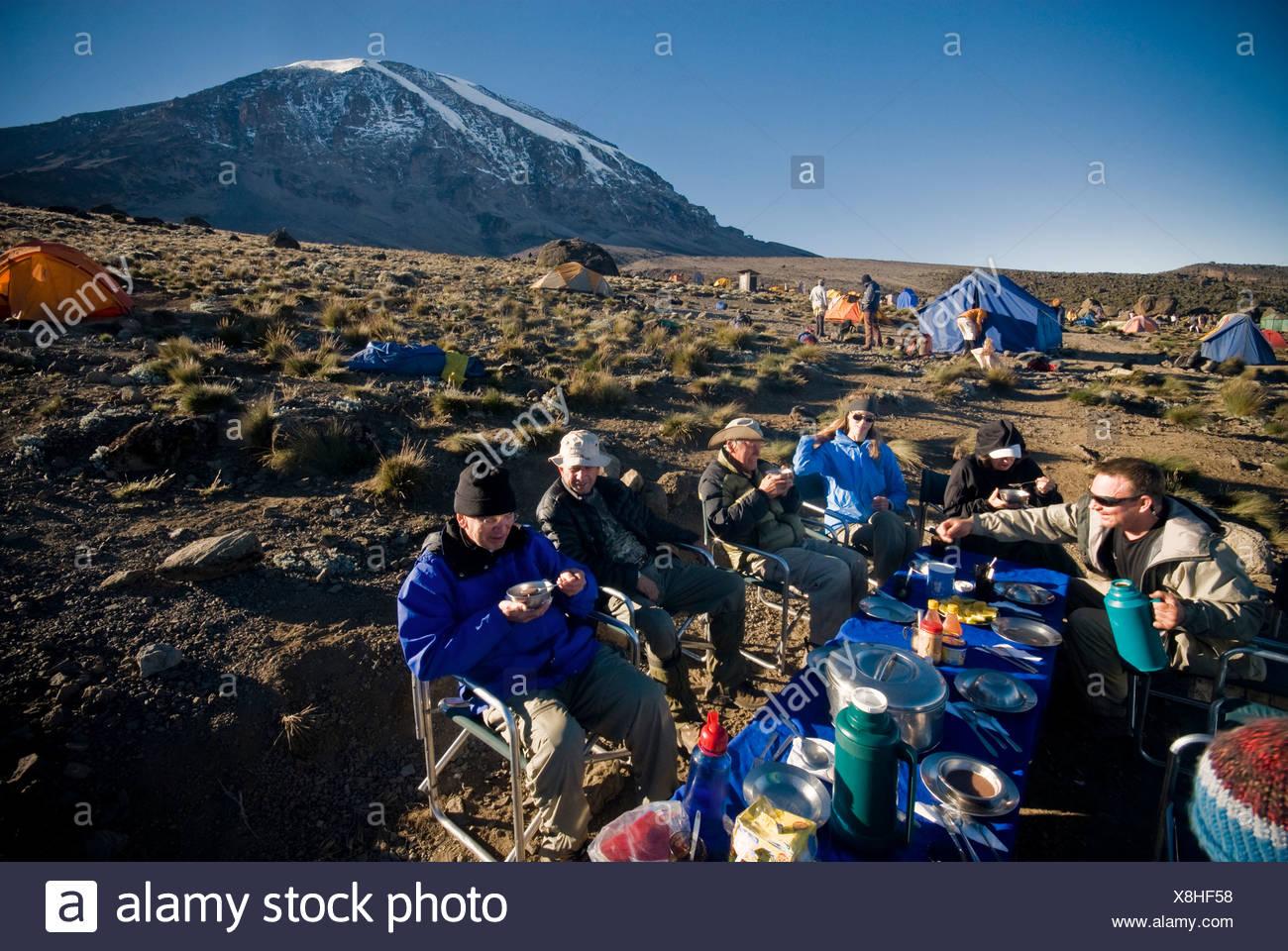 Un grupo de excursionistas tienen un agradable desayuno al amanecer sobre 1000 pies por debajo de la cima del Mt. Kilimanjaro. Imagen De Stock