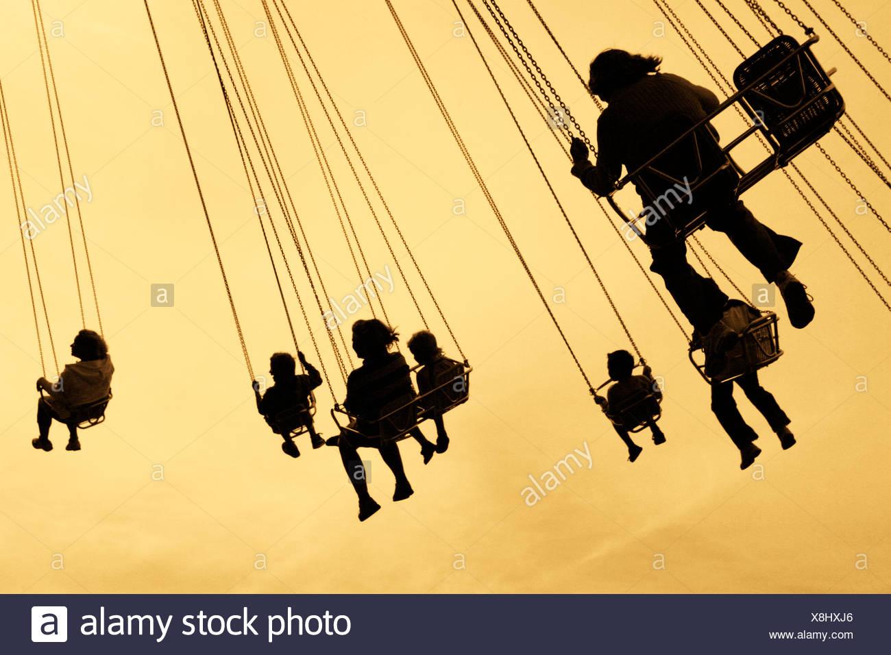 Suecia Vastra Gotaland, Gotemburgo, siluetas de personas en carrusel en el parque de atracciones Liseberg Imagen De Stock