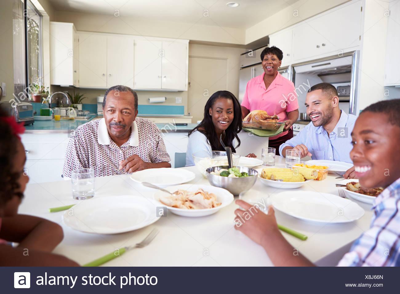 Familia Multi-Generation sentado en torno a una mesa comiendo comida Imagen De Stock