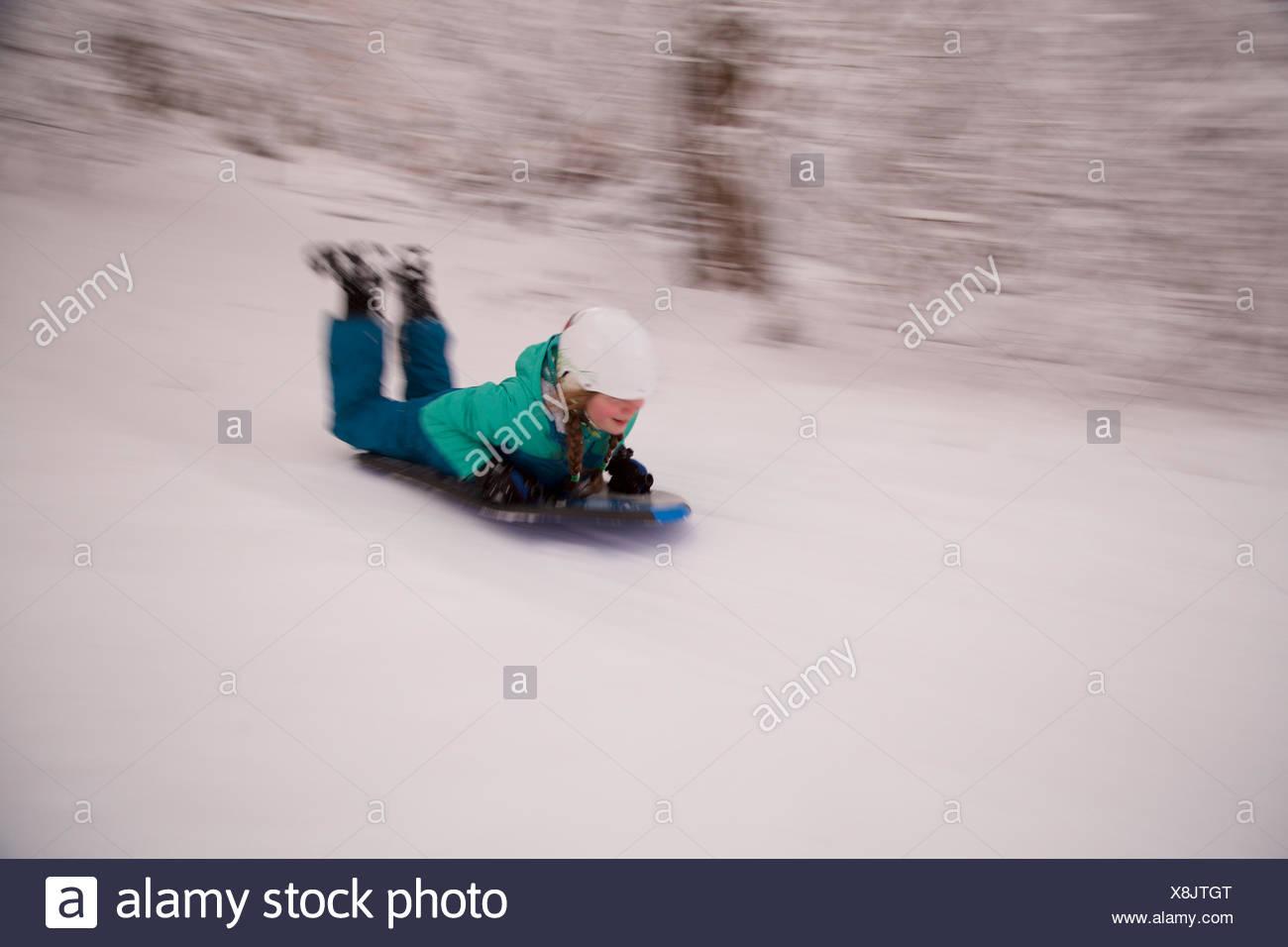 Una chica joven de trineo cuesta abajo con un casco. Imagen De Stock