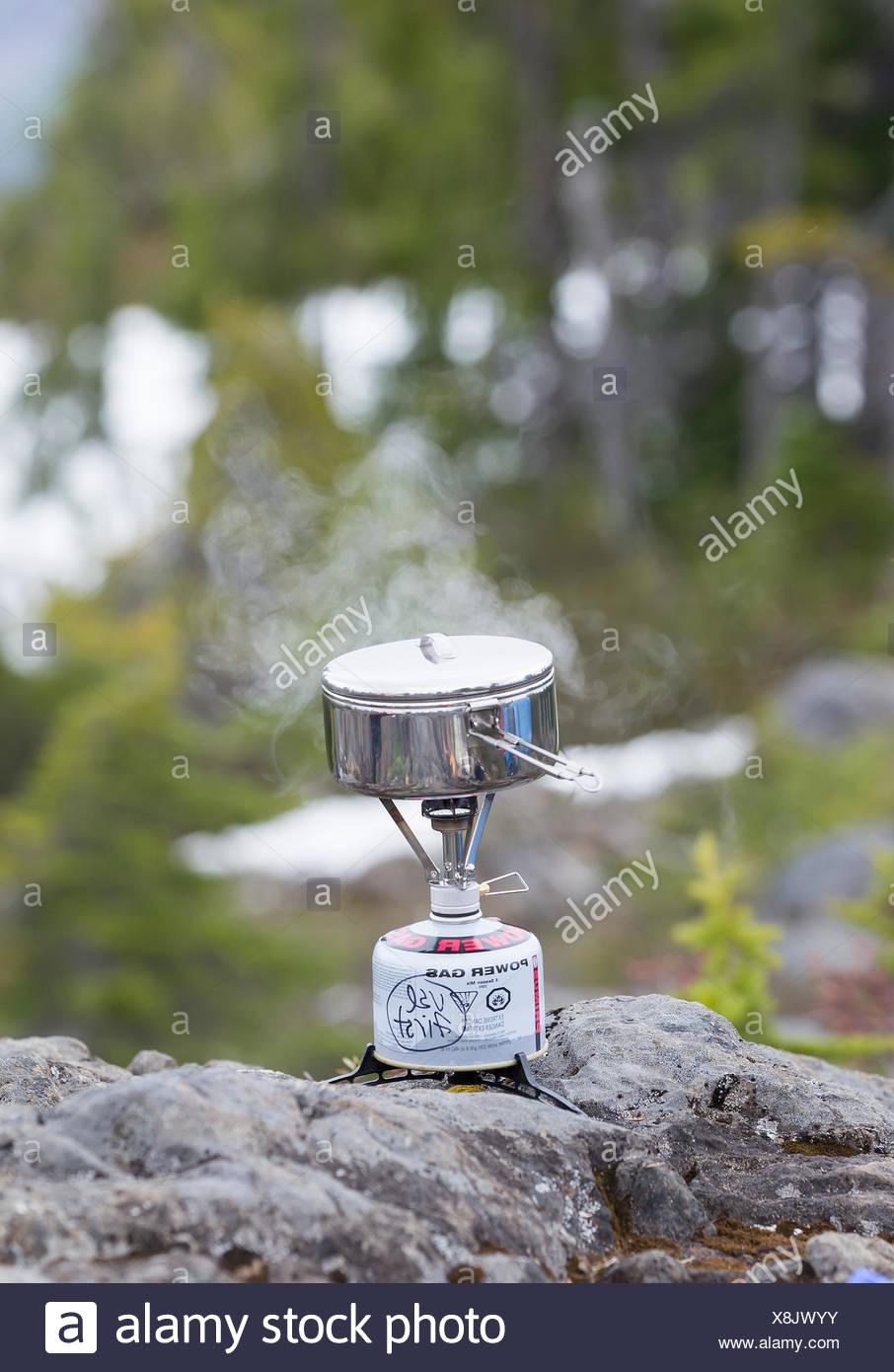 Cena hierve en una pequeña estufa mientras cook camping en la meseta de Lee, la isla de Vancouver, British Columbia, Canadá. Imagen De Stock