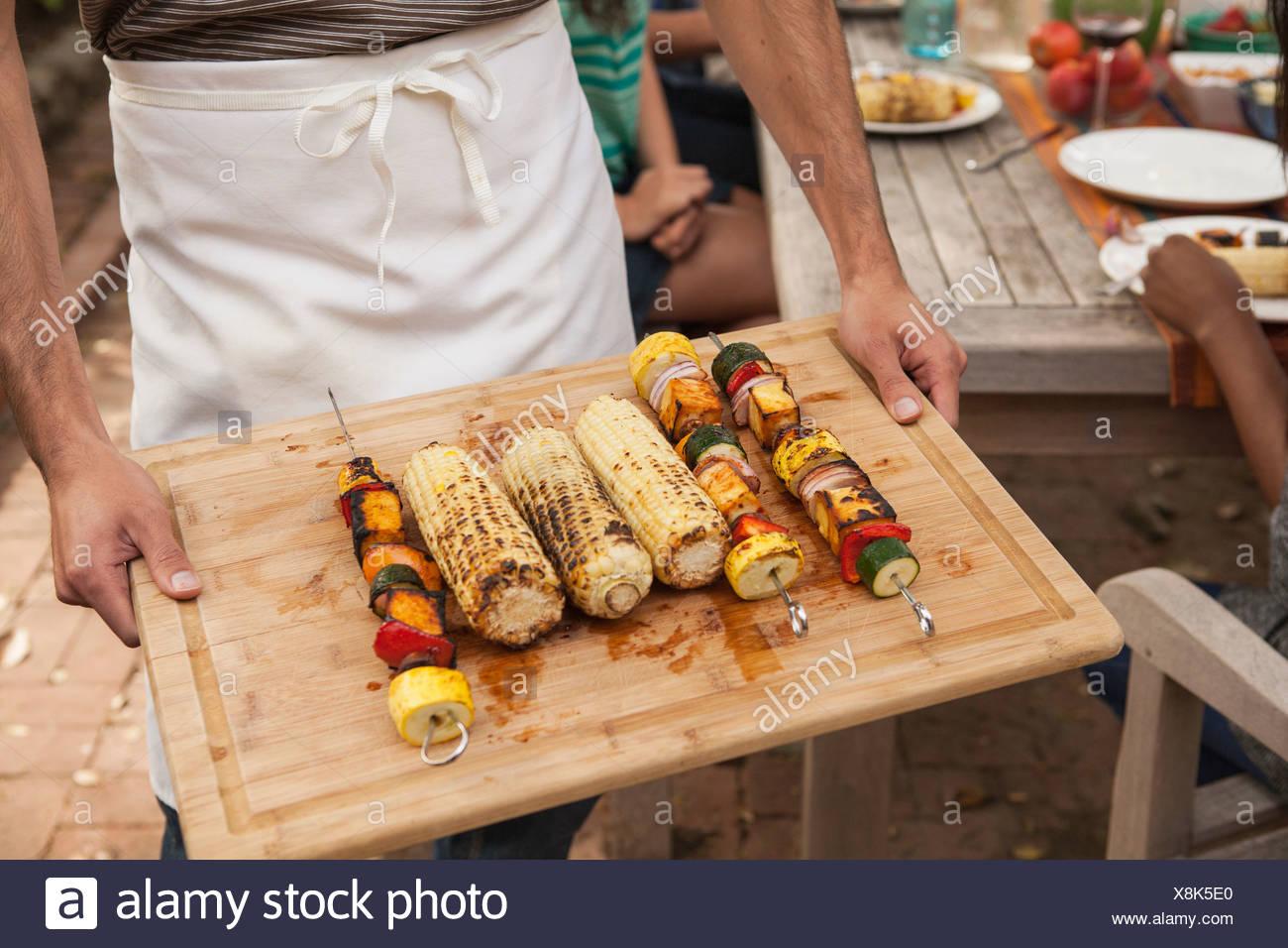 Hombre sujetando una bandeja de pinchos de verduras a la brasa y la mazorca de maíz Imagen De Stock