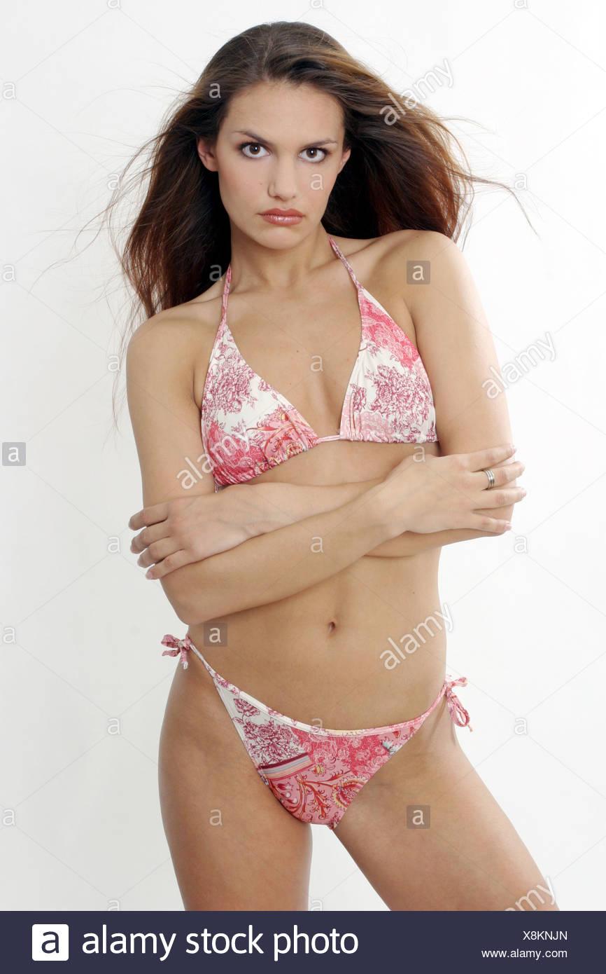 Morena, longhaired mujer vistiendo bikini, cruzando los brazos, mirando a la cámara. Foto de stock