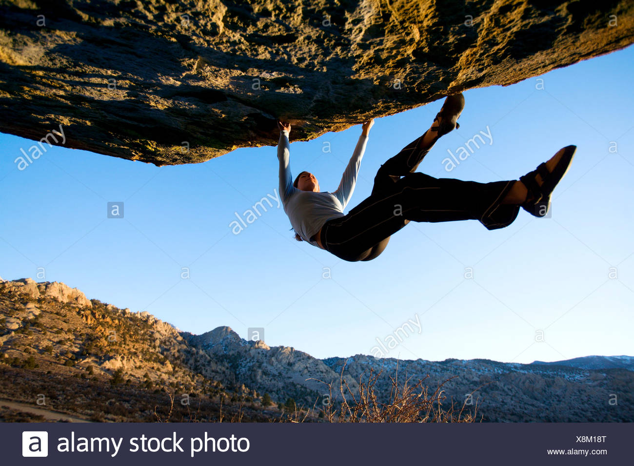 Mujer trepar rocas en un saliente Imagen De Stock
