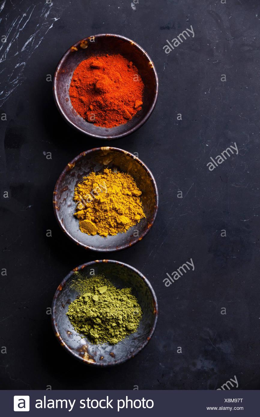 Especias el Curry, pimentón, Matcha té en el fondo de mármol oscuro Imagen De Stock