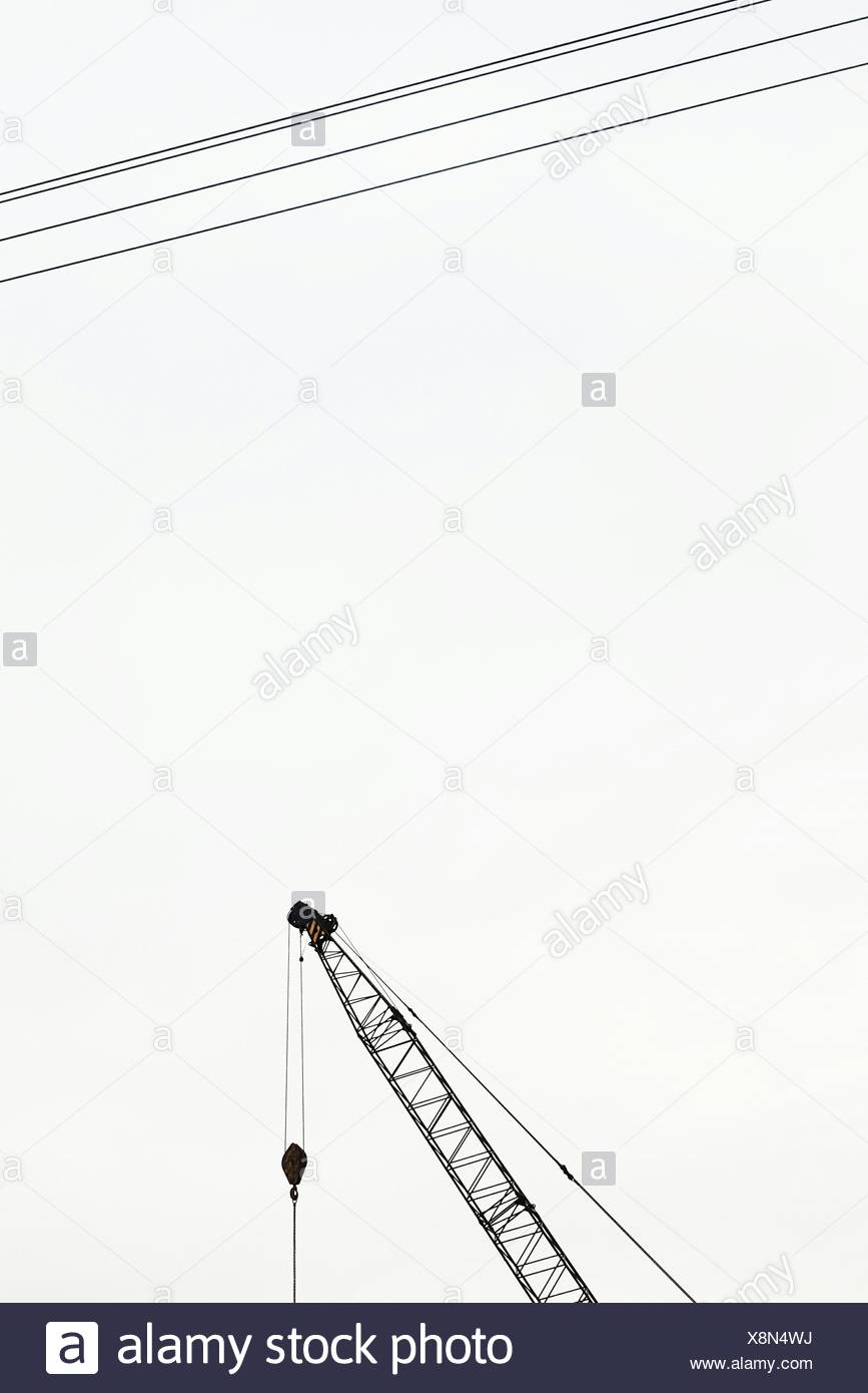Ángulo de visión baja de la grúa y los cables eléctricos contra el cielo claro Imagen De Stock