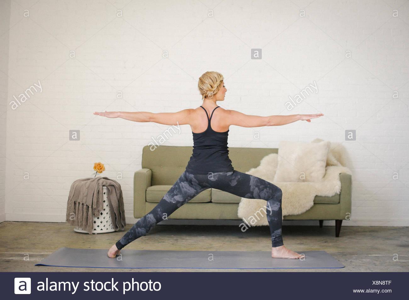Una mujer rubia en un leotard negro y calcetas de pie sobre una estera del yoga en una habitación, piernas y brazos estirados. Imagen De Stock