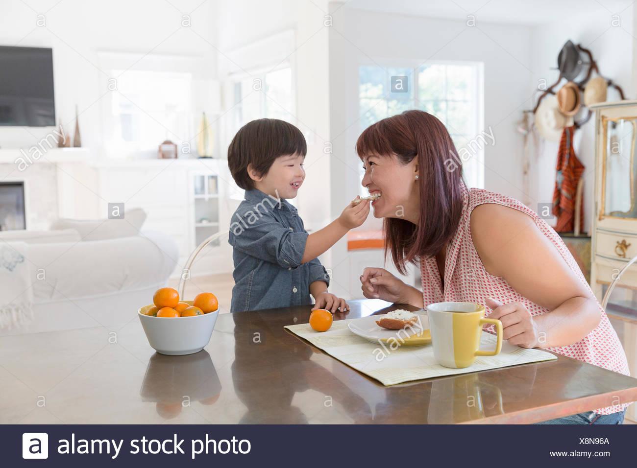 Juguetón hijo alimentar la madre en la mesa de comedor Imagen De Stock