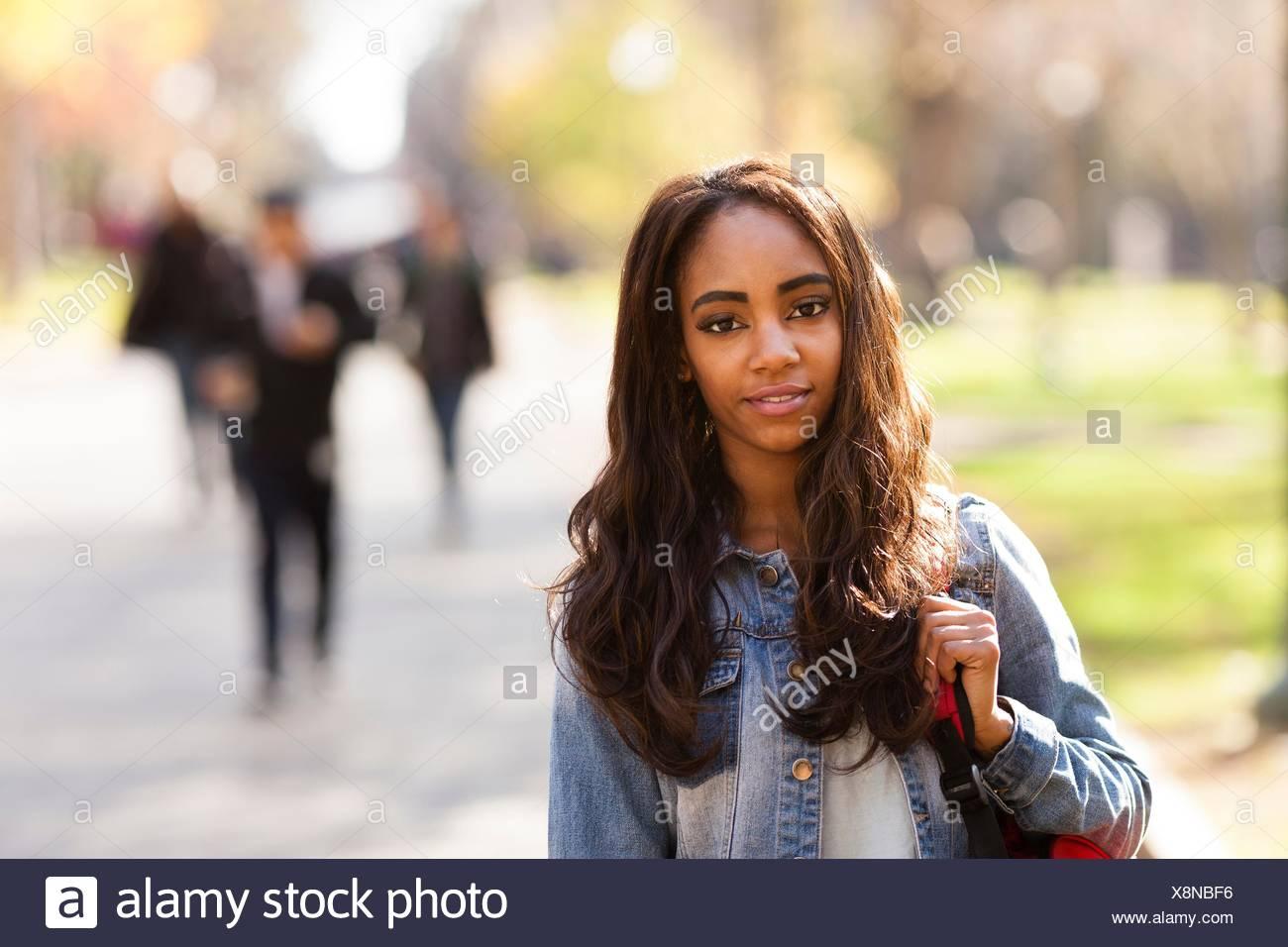 Retrato de mujer joven con largo pelo castaño vistiendo chaqueta denim mirando a la cámara sonriendo Imagen De Stock