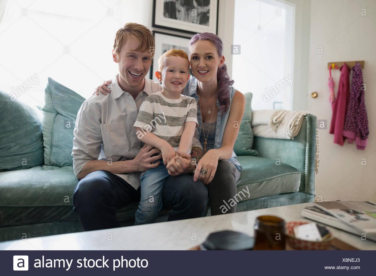 Retrato sonriente joven familia en el sofá en el salón Imagen De Stock