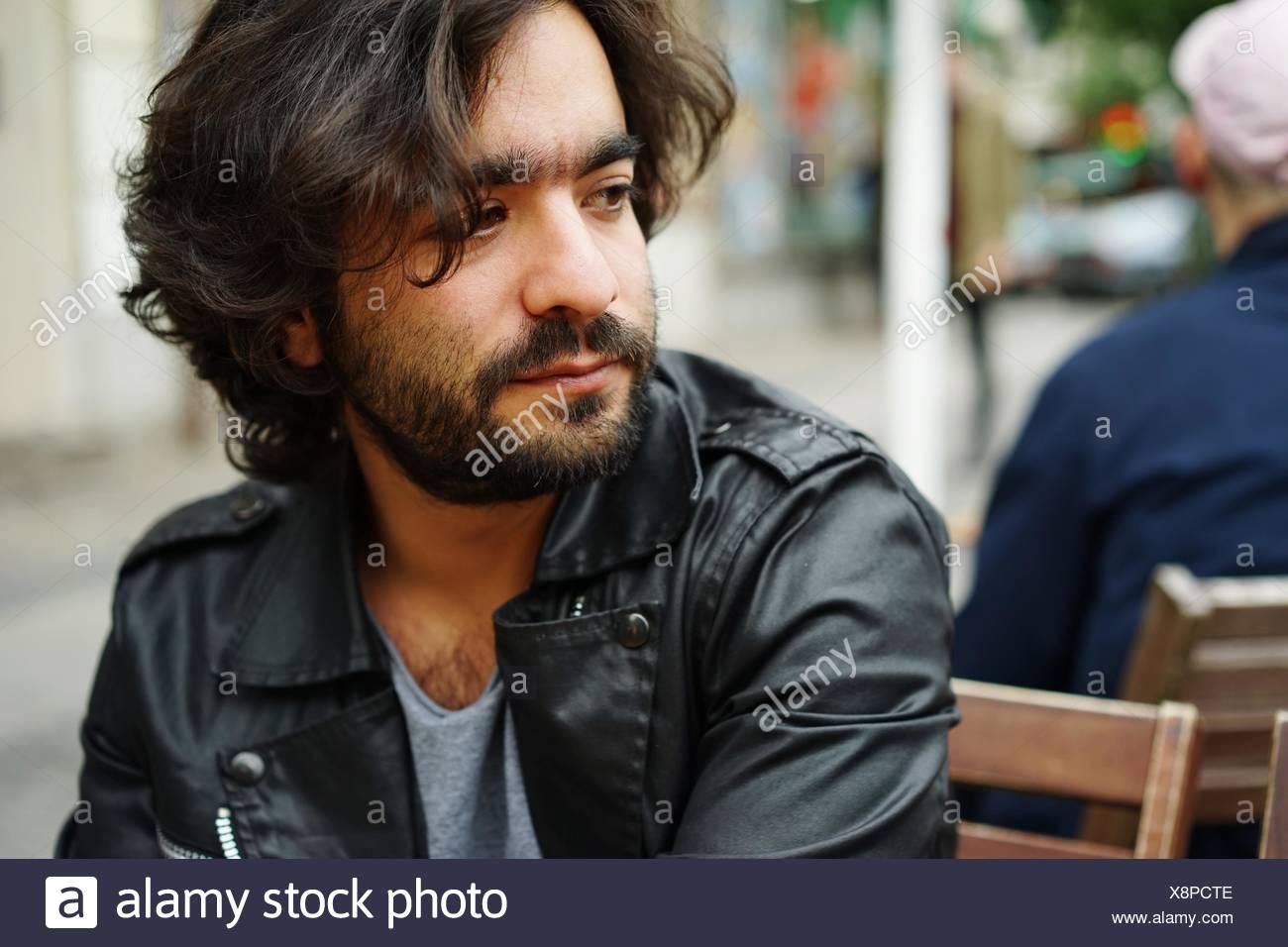 Hombre mirando lejos al café en la acera Imagen De Stock