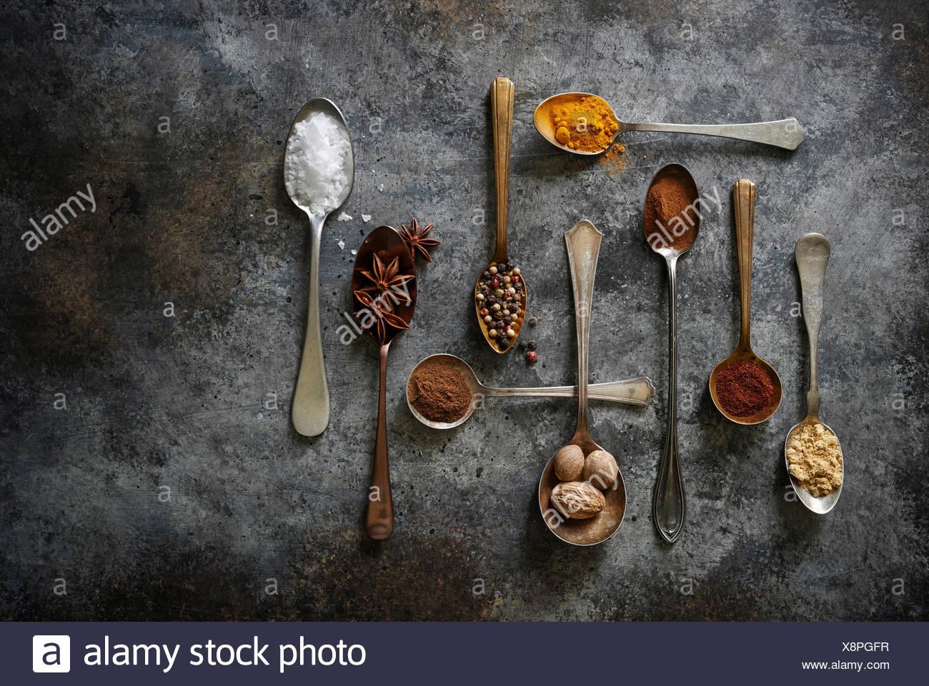 Una matriz de bonito hornear y cocinar las especias en el vintage cucharas sobre una superficie oscura de estilo rústico. Imagen De Stock