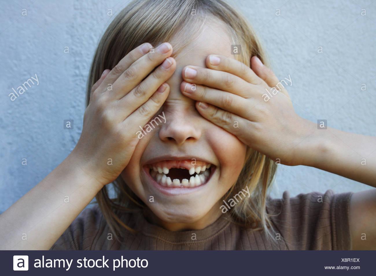 Chico con gap sonrisa dentada con las manos cubriéndose los ojos Foto de stock