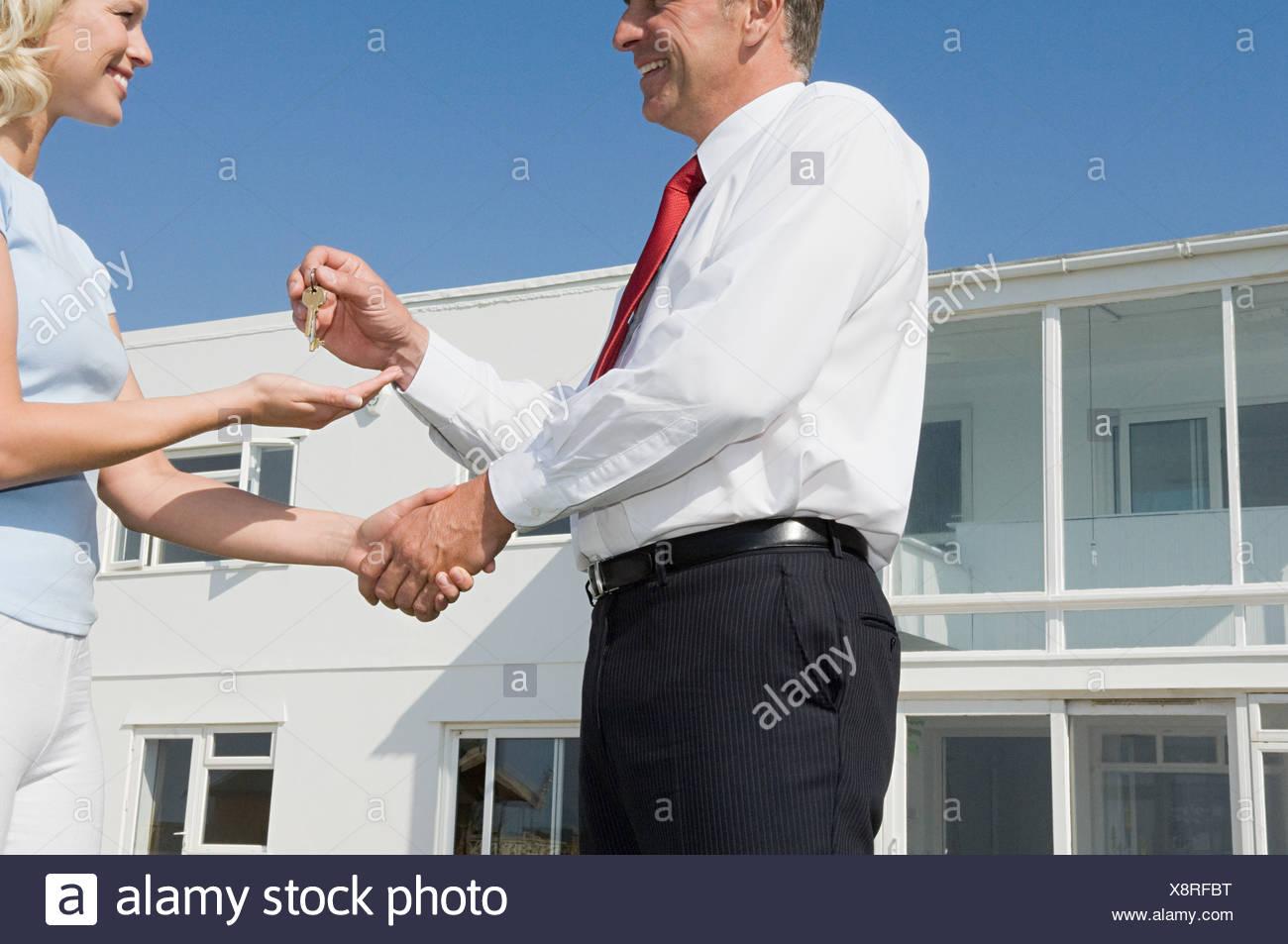 Mujer y estate agent agitando las manos Imagen De Stock