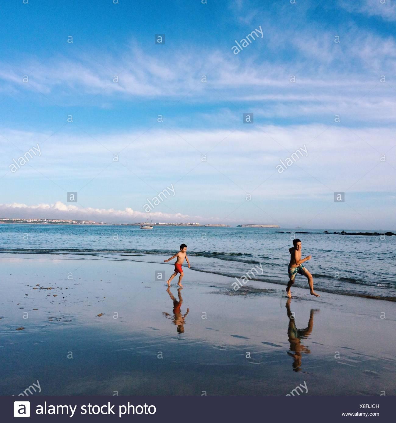 Dos niños corriendo en la playa Imagen De Stock