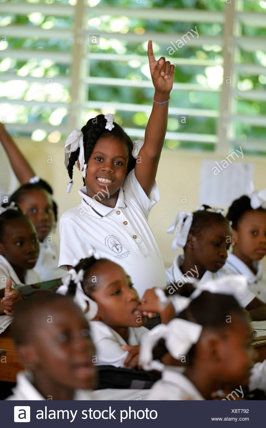 Colegiala levantando su mano en clase, la clase de la Escuela Primaria Basile Moreau, Carrefour, Port-au-Prince, el Departamento Ouest Imagen De Stock