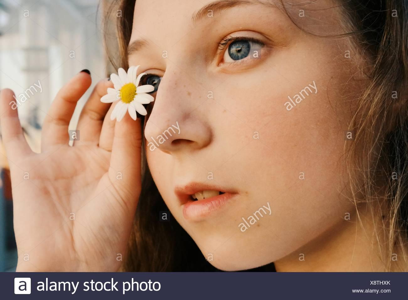 Primer plano de Una Chica sujetando una flor de margarita cerca de su ojo Imagen De Stock