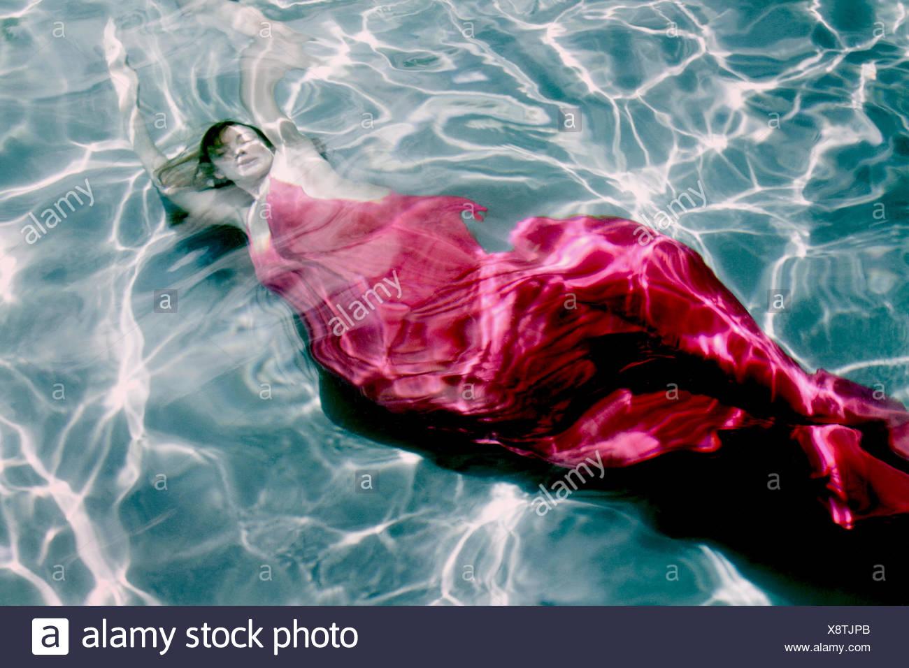 Vista superior de una mujer en un vestido nadando bajo el agua Foto de stock