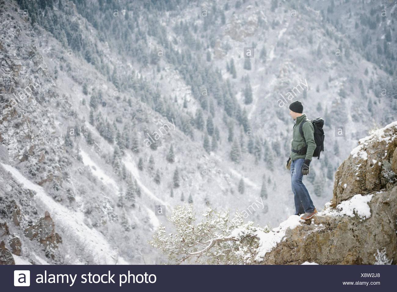 Un hombre senderismo en las montañas de pie mirando hacia un valle. Imagen De Stock