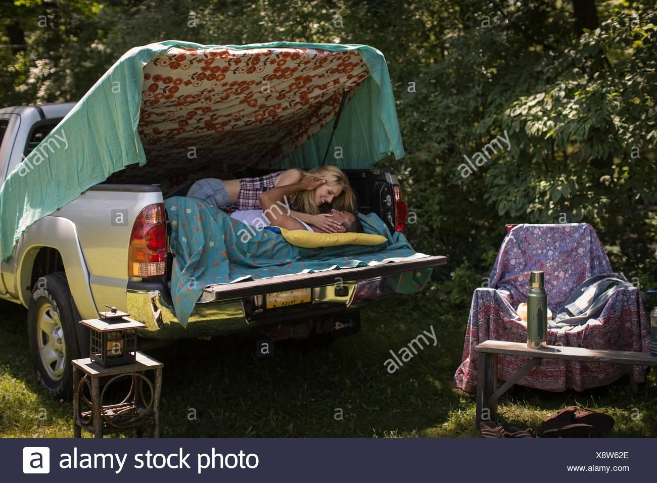 Mujer joven besar novio en pick up boot mientras camping Imagen De Stock