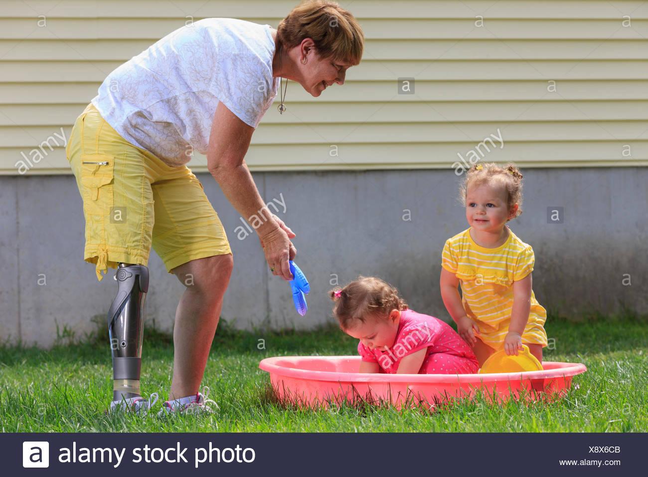 Abuela con una pierna protésica jugando con sus nietos en una piscina infantil Imagen De Stock