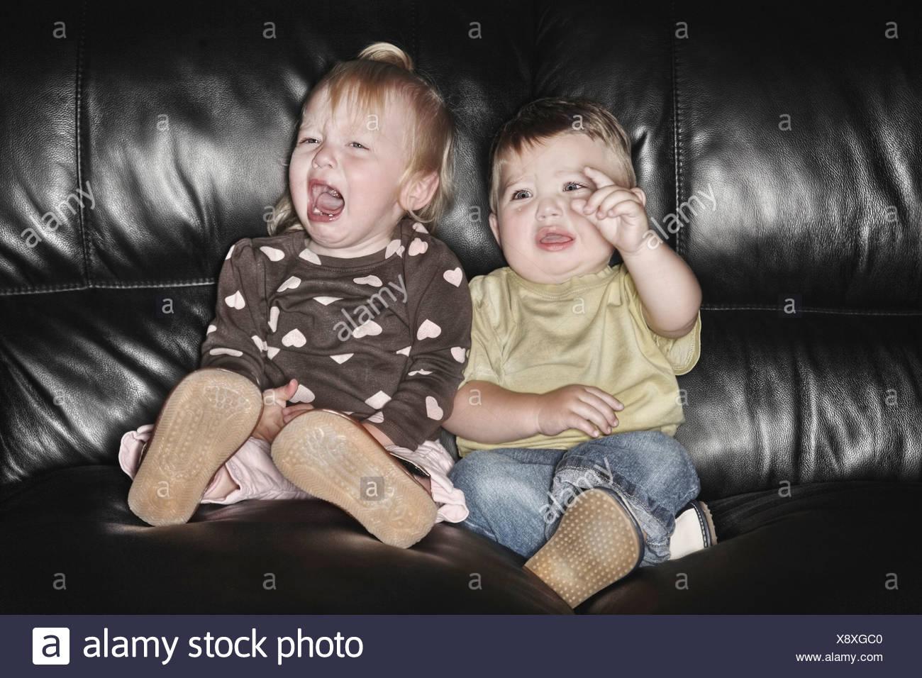 Edmonton, Alberta, Canadá; dos niños sentados en el sofá y llorando juntos Foto de stock