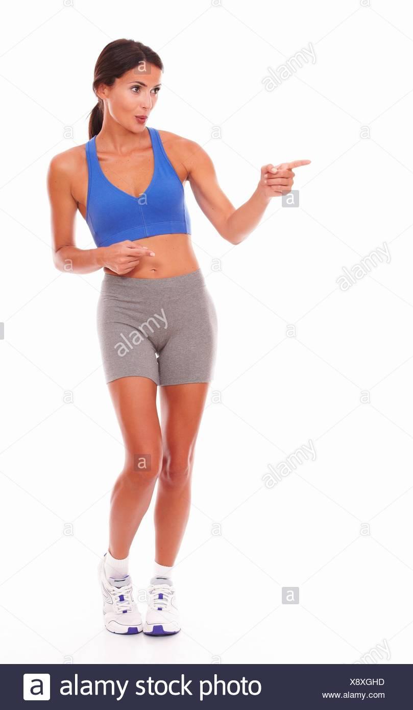 951298b9c Bonita mujer adulta en su ropa deportiva señalando a su derecho contra el fondo  blanco - copyspace.