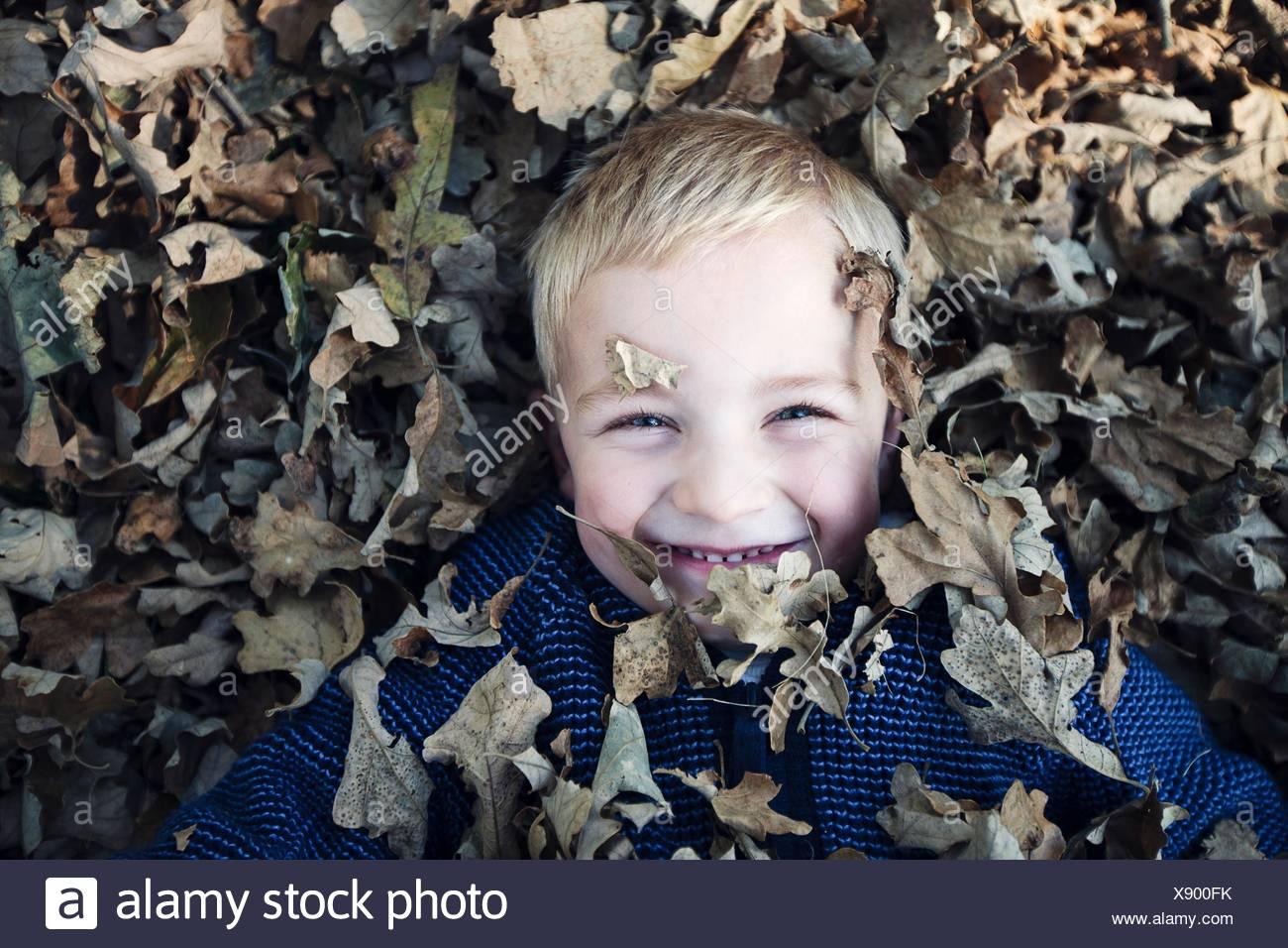 Vista aérea del niño acostado cubierto de hojas de otoño mirando a la cámara sonriendo Imagen De Stock