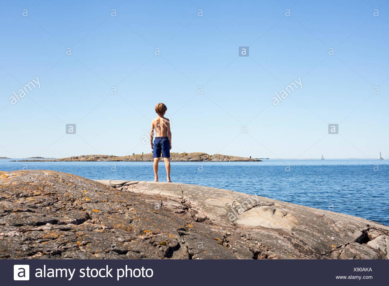 Suecia, Uppland Runmaro, Barrskar, vista trasera de boy (6-7) mirando el mar Imagen De Stock
