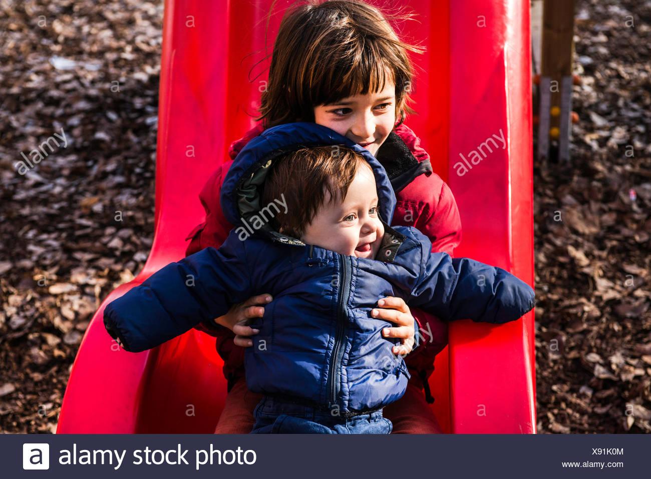 Hermano bebé niño sosteniendo en playground diapositiva Imagen De Stock