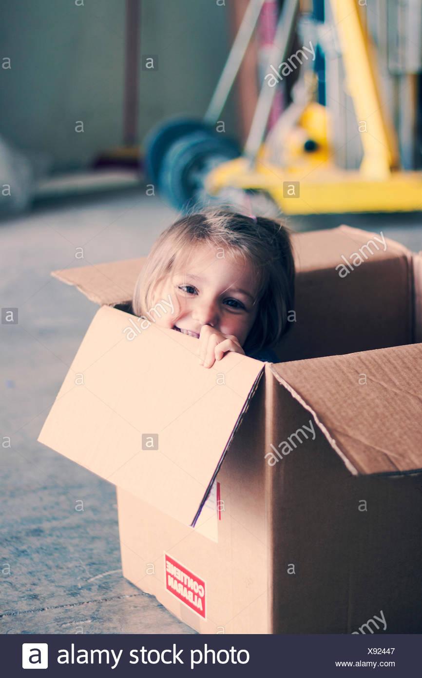 Chica sonriente sentado dentro de una caja de cartón Imagen De Stock