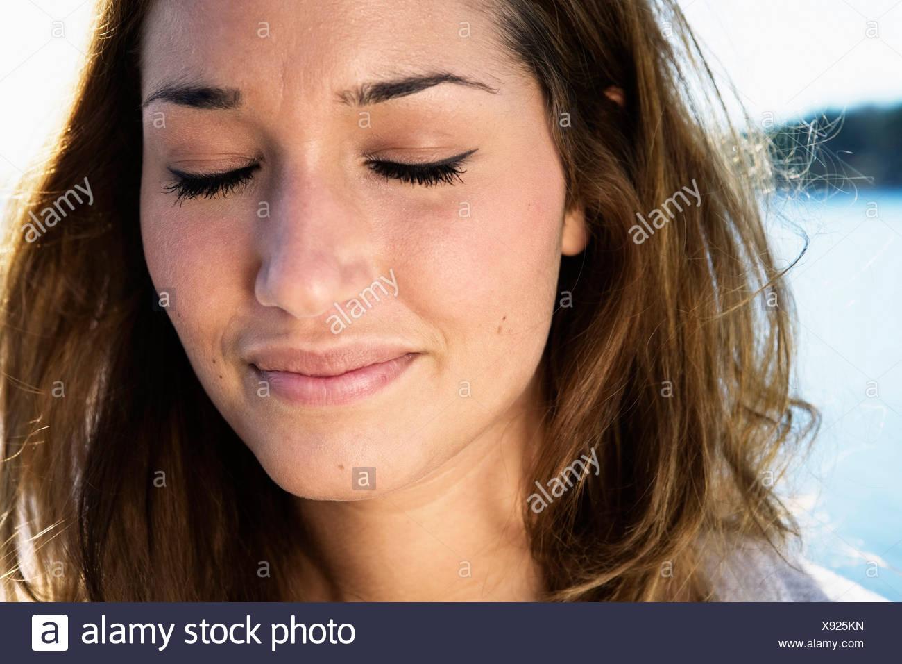 Mujer con cabello oscuro cerrando sus ojos Foto de stock