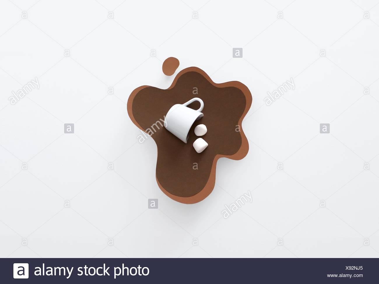 Mug conceptual derribados, tumbado en una piscina de papel hecha de chocolate caliente con malvaviscos Imagen De Stock