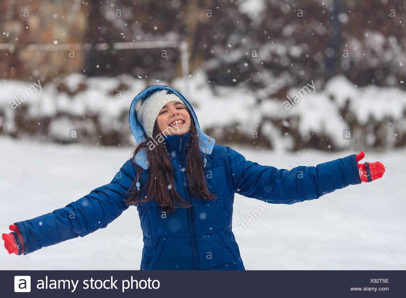 Chica con los brazos estirados jugando en la nieve Foto de stock