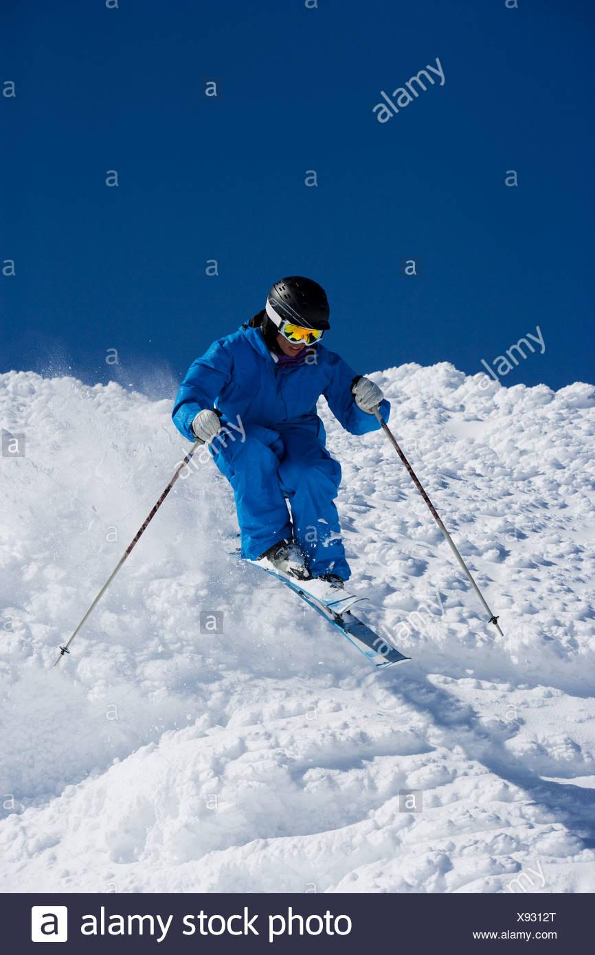 Hombre en Azul esquí cuesta abajo. Foto de stock