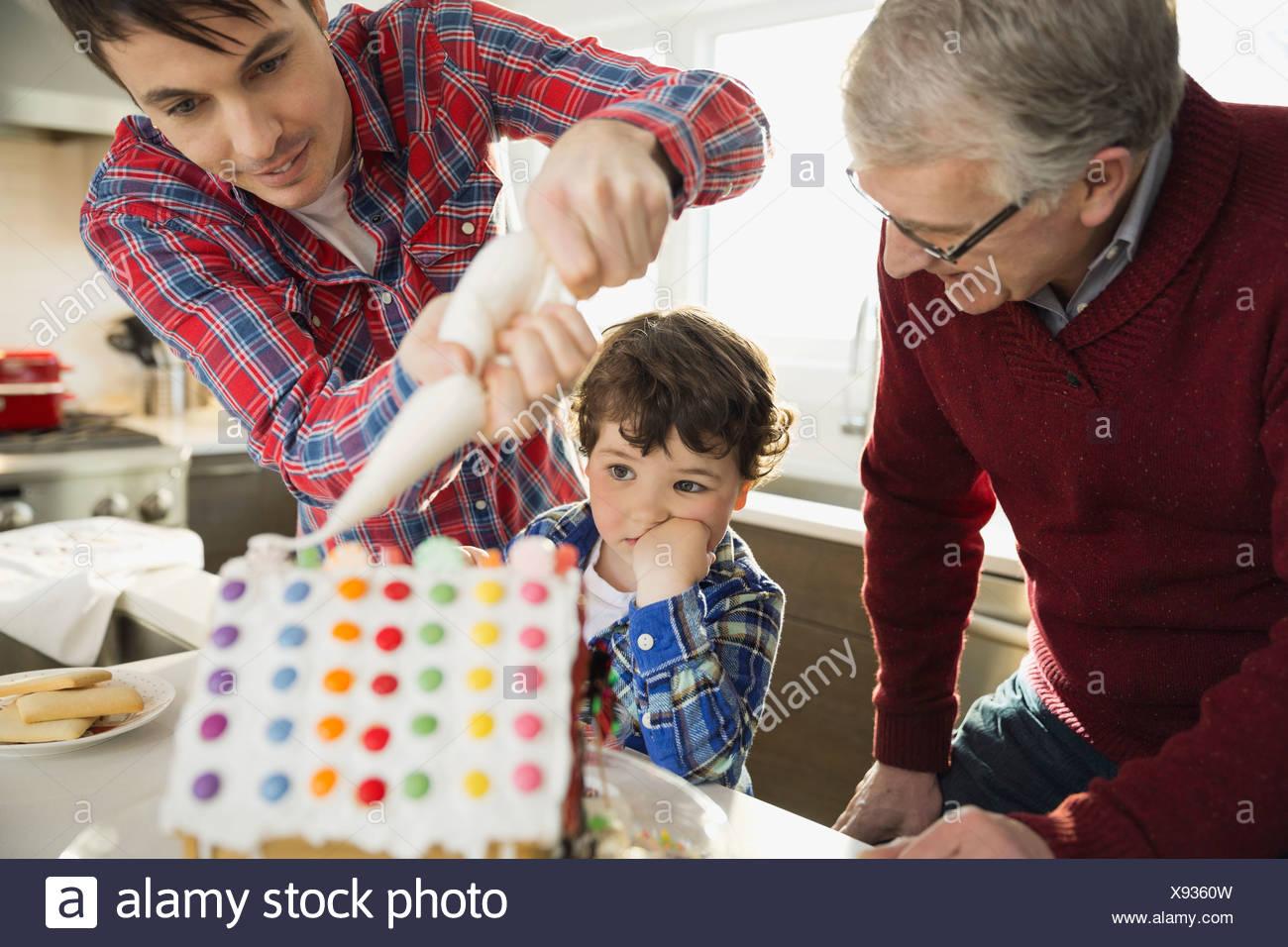 Chico viendo como padre decora la casa de pan de jengibre Imagen De Stock