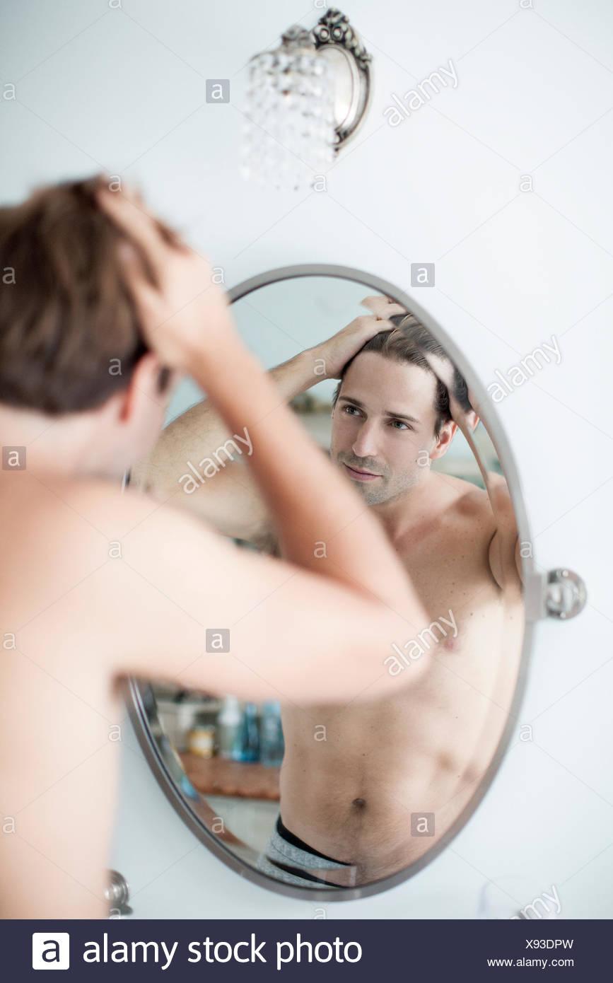 Hombre examinando el indicador en espejo Imagen De Stock