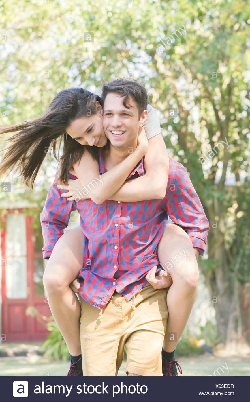 La pareja al aire libre, hombre mujer dando un paseo piggyback Imagen De Stock