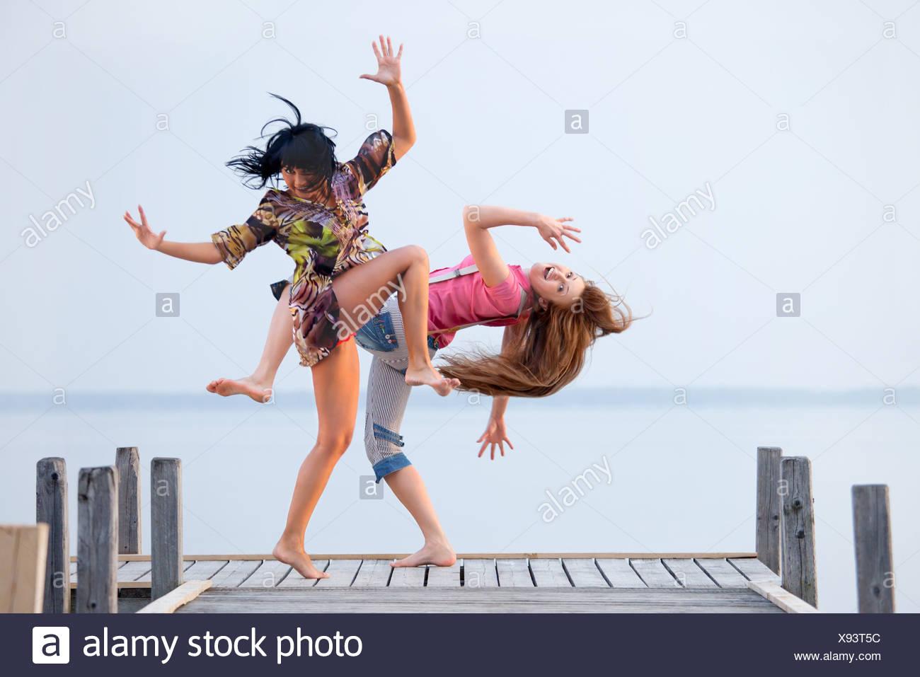 Dos niñas están bailando en el fondo del agua y el cielo Imagen De Stock