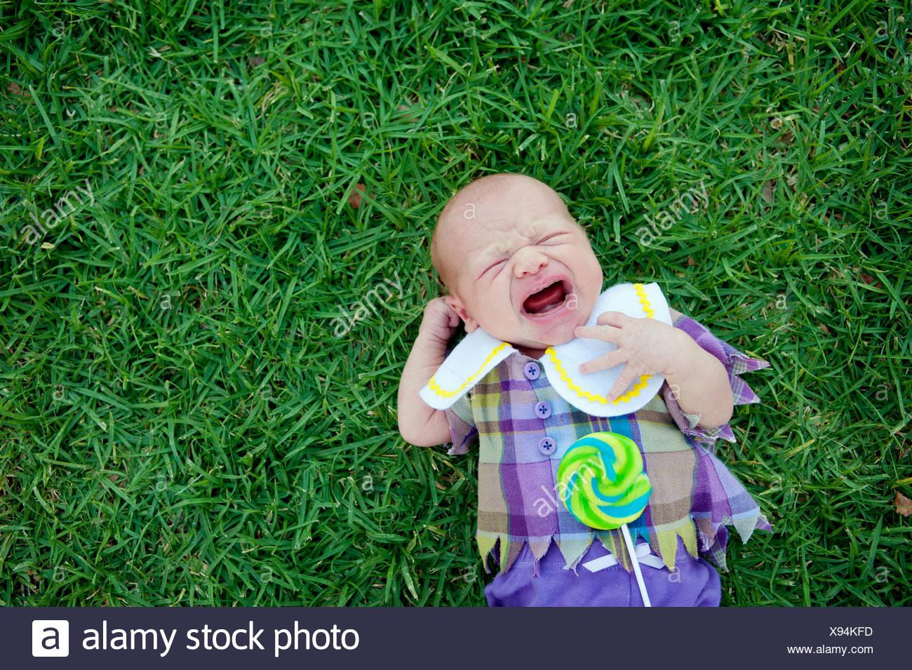 Bebé acostado en el pasto, llorando Imagen De Stock