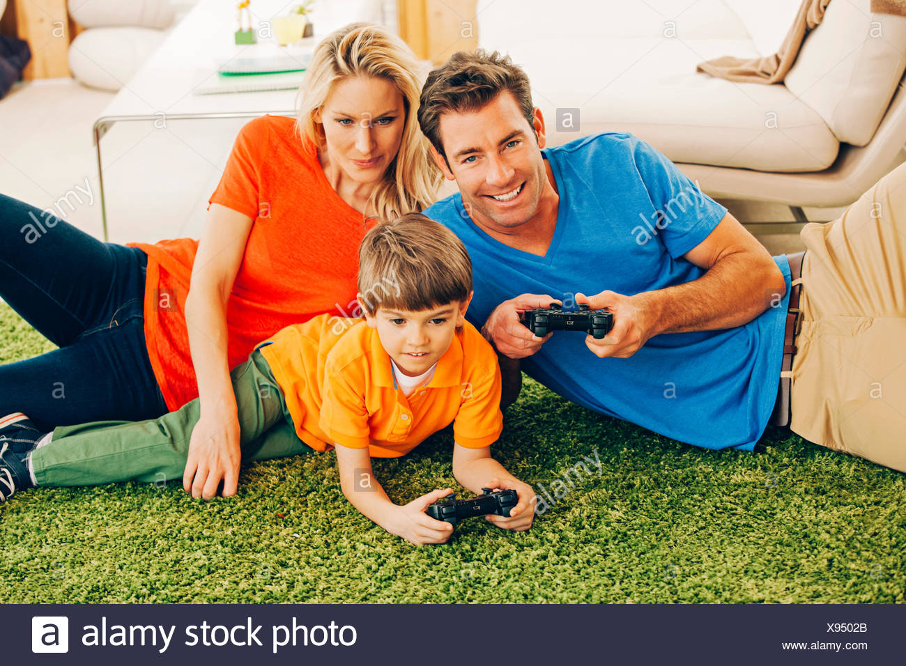 Familia de tres jugar video juego en el salón Imagen De Stock