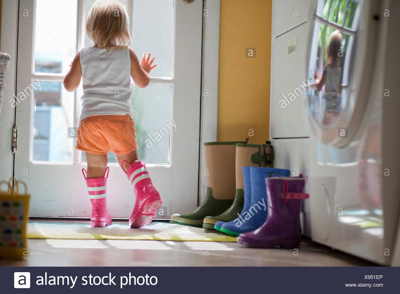 Hembra usando botas de goma niño mirando por la ventana de la puerta trasera Imagen De Stock