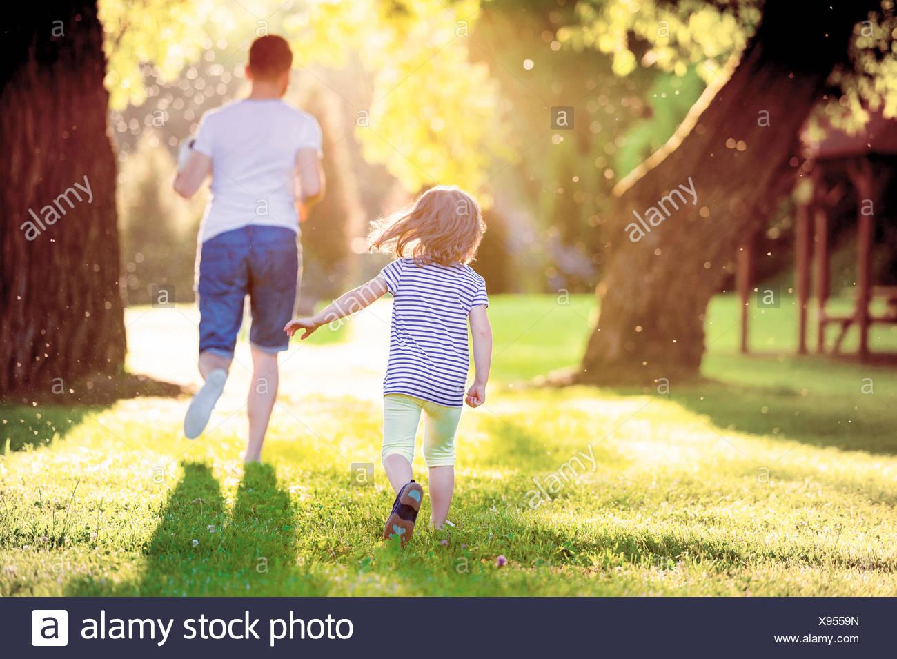 Vista posterior del padre y su pequeña hija se ejecuta en una pradera en el parque Imagen De Stock