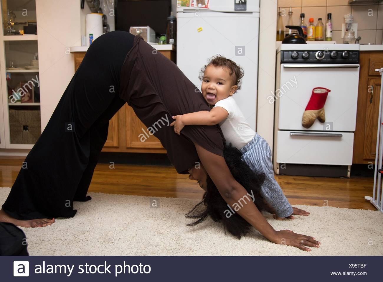 Mujer adulta media ejercen sobre la alfombra con infante hija Imagen De Stock