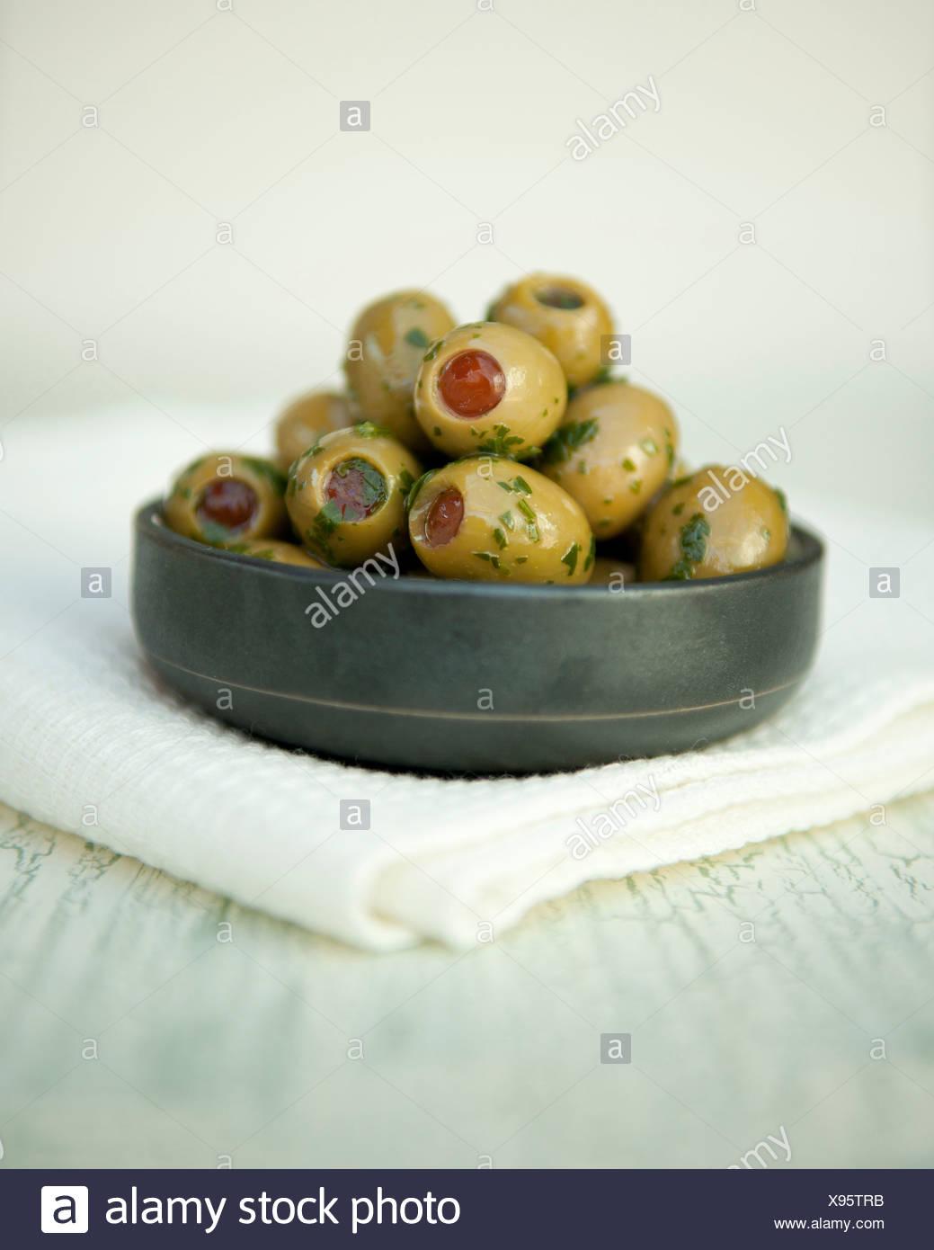 Aceitunas verdes rellenas con pimientos rojos con aceite de oliva y las hierbas en una olla Foto de stock
