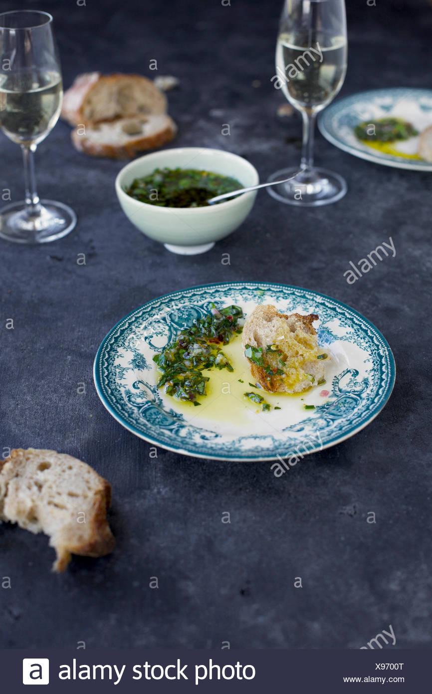 Salsa Verde de estilo italiano se sirve con el pan y el vino blanco. Fotografiado desde vista frontal sobre un fondo gris oscuro. Imagen De Stock